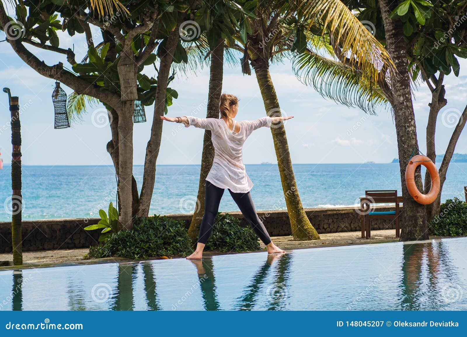 A menina bonita está praticando a ioga, meditação, estando a pose da parte traseira no recurso com paisagem do oceano em Indonési