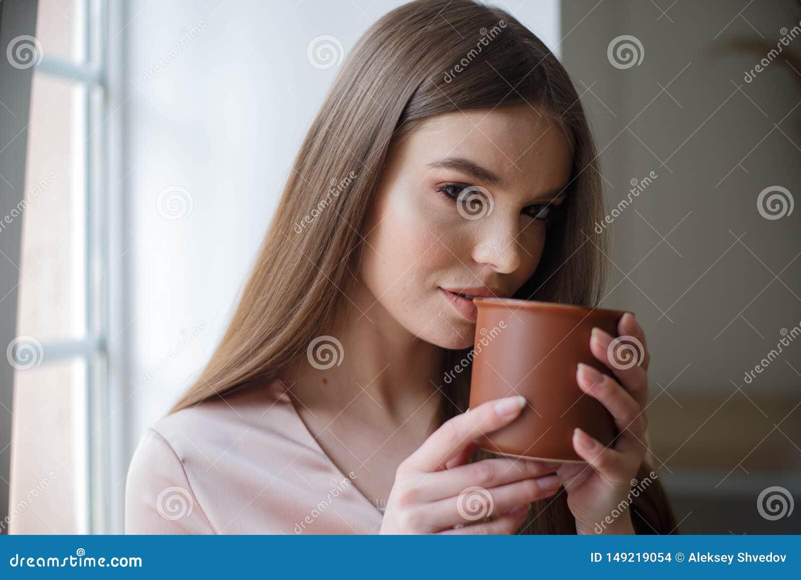A menina bonita est? bebendo o caf? e est? sorrindo ao sentar-se no caf?