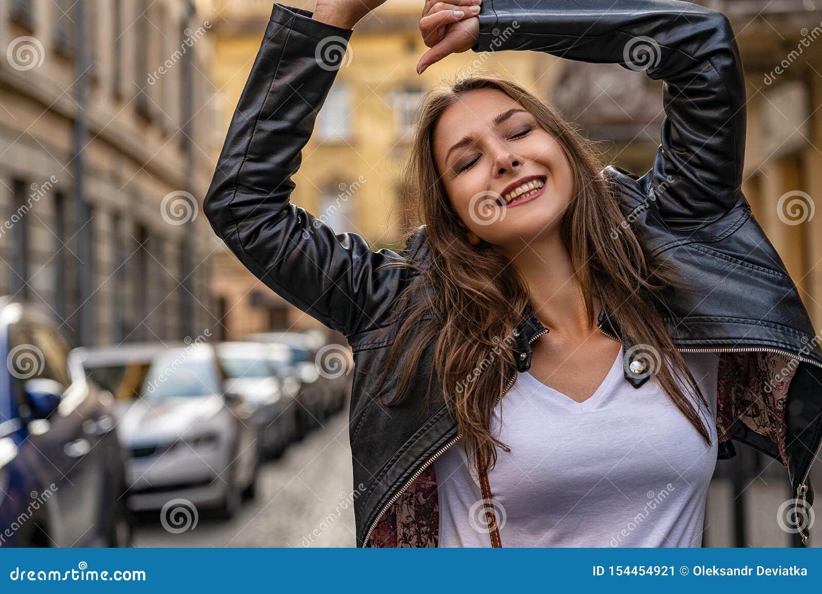 A menina bonita exulta na rua da cidade velha Sessão fotográfica do estilo de vida da forma com modelo fêmea novo