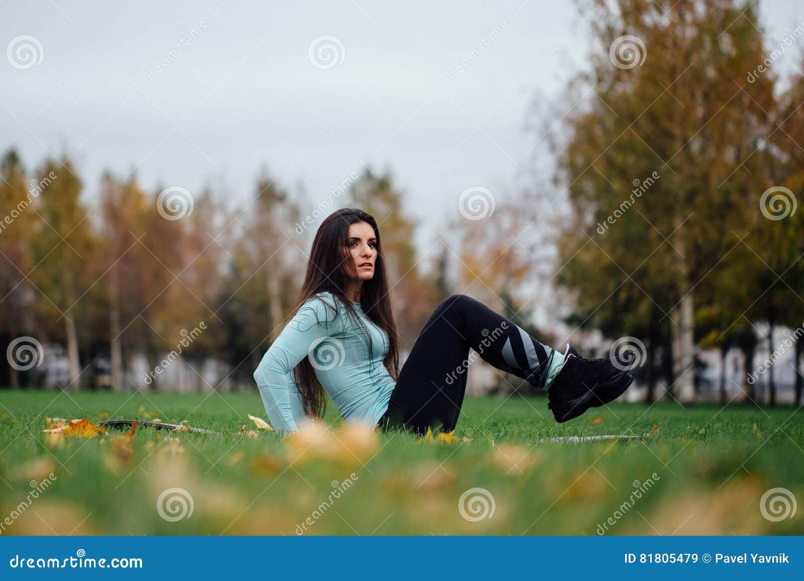A menina bonita faz exercícios com a imprensa na grama