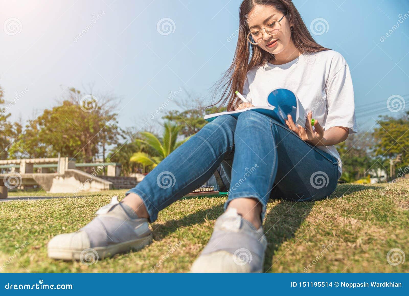 Menina bonita na floresta do outono que l? um livro coberto com uma cobertura morna uma mulher senta-se perto de uma árvore em um