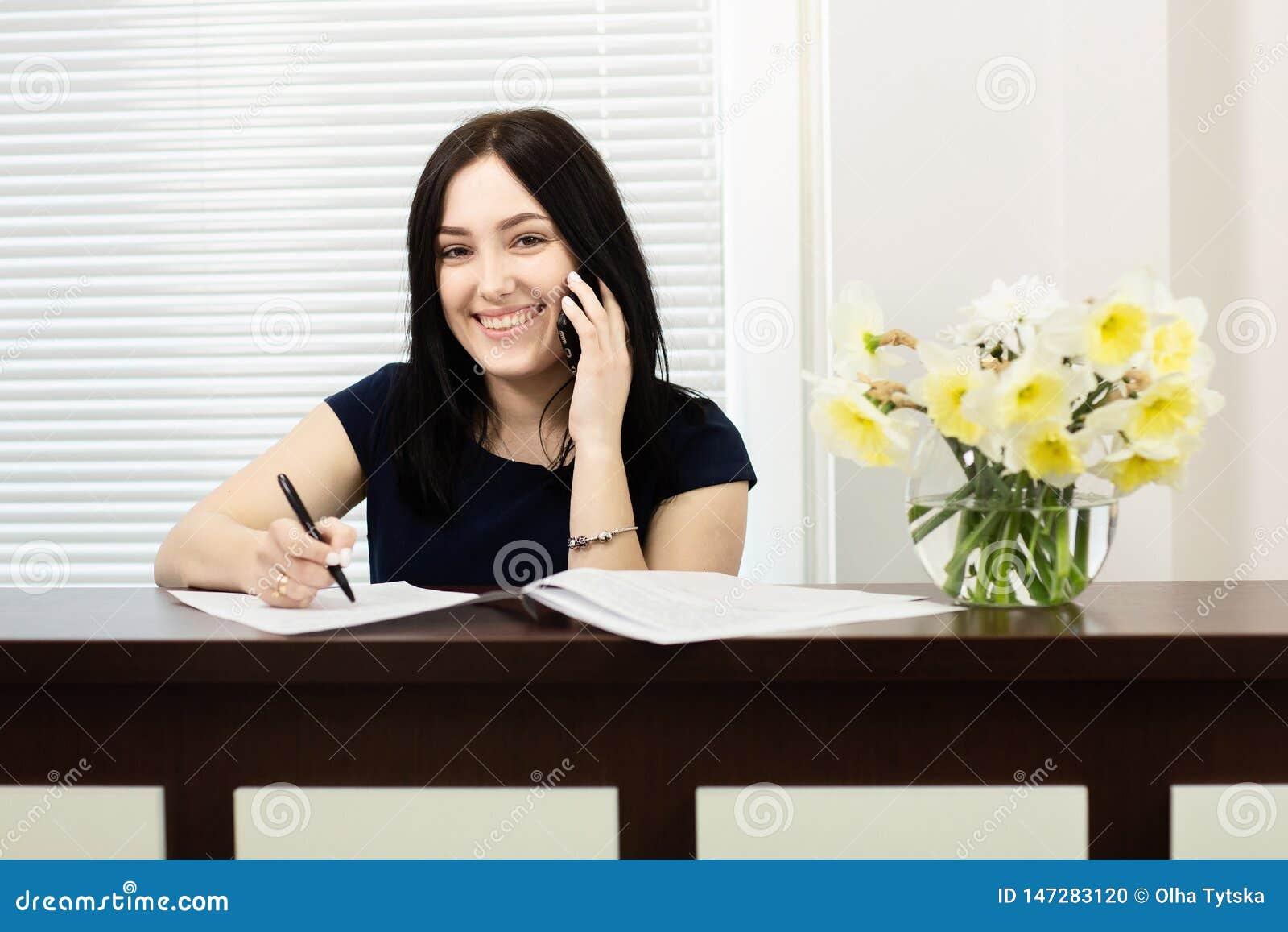 Menina bonita na mesa de recep??o que responde ? chamada no escrit?rio dental