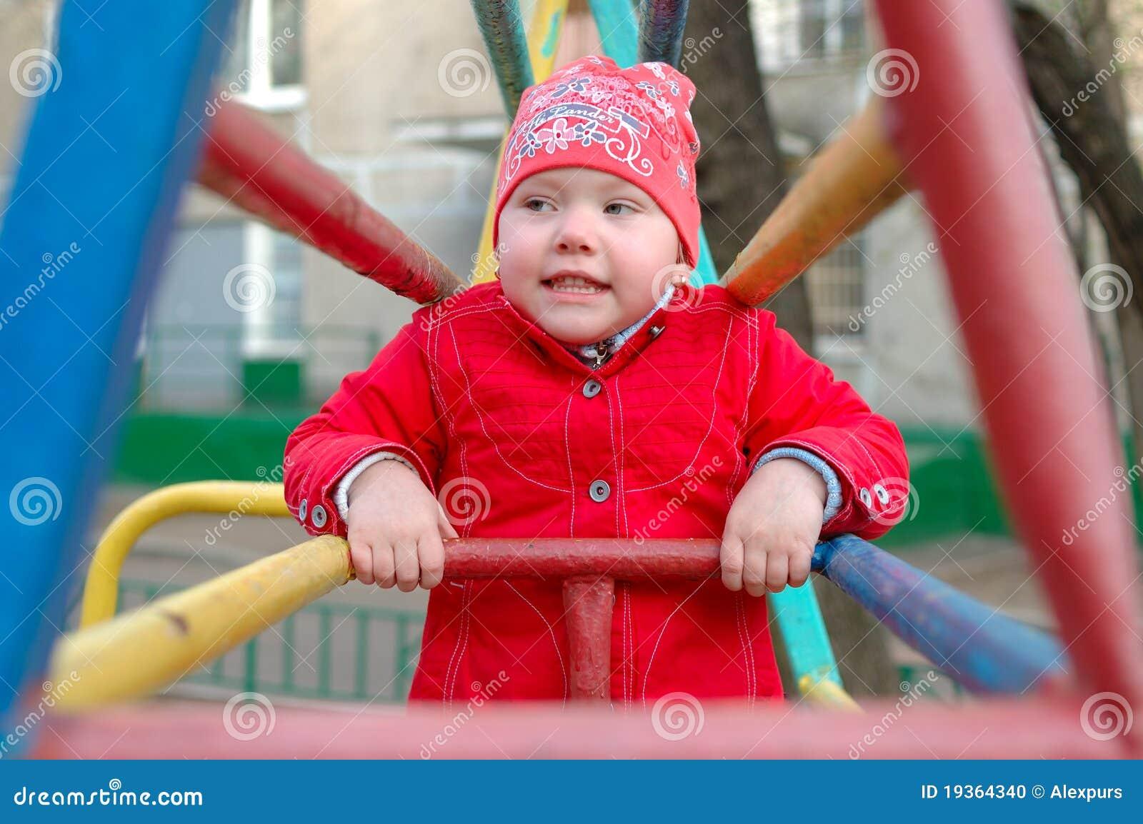 Menina bonita nas barras de macaco do campo de jogos.