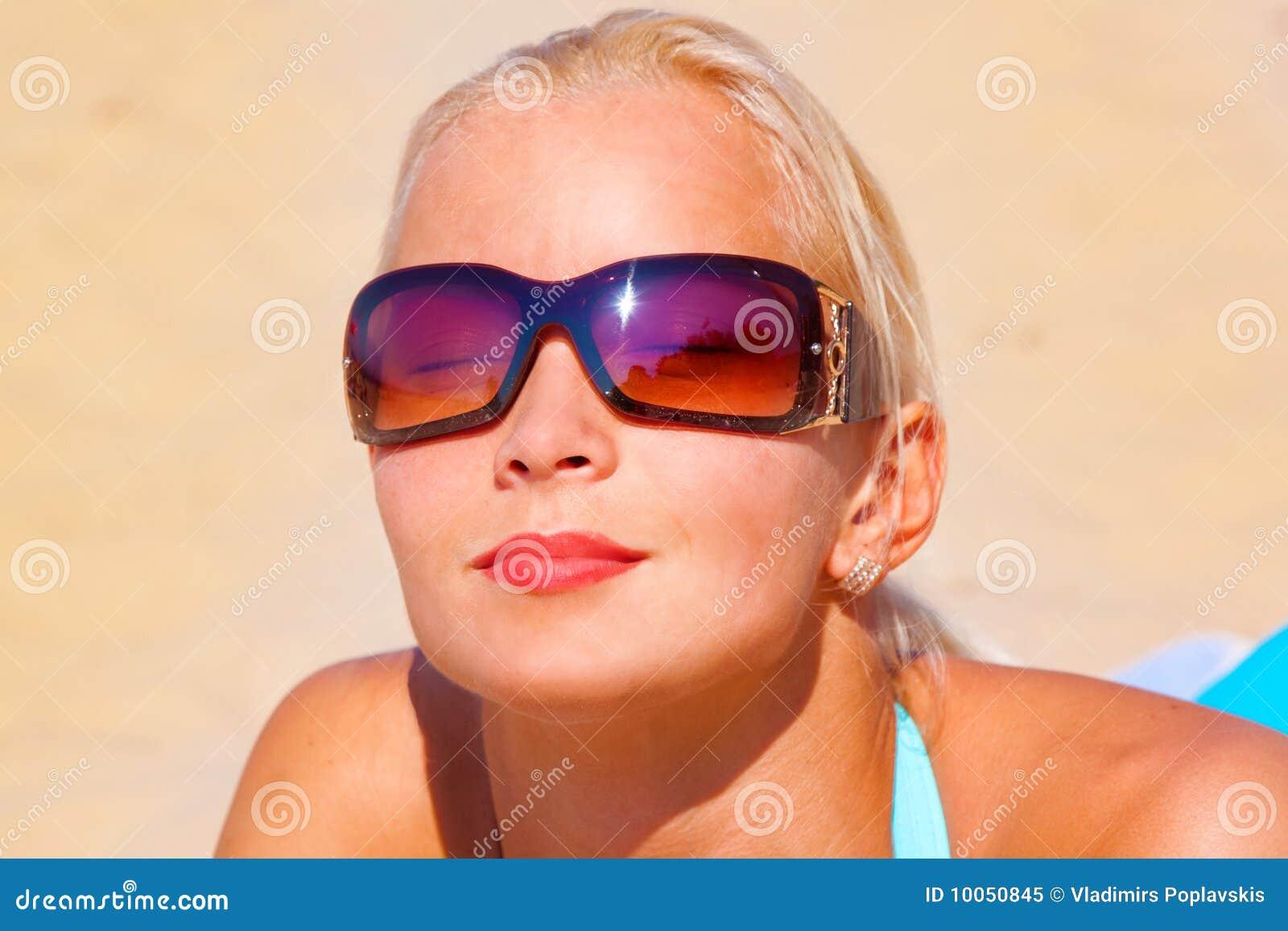 Menina bonita no biquini que coloca o OM a praia