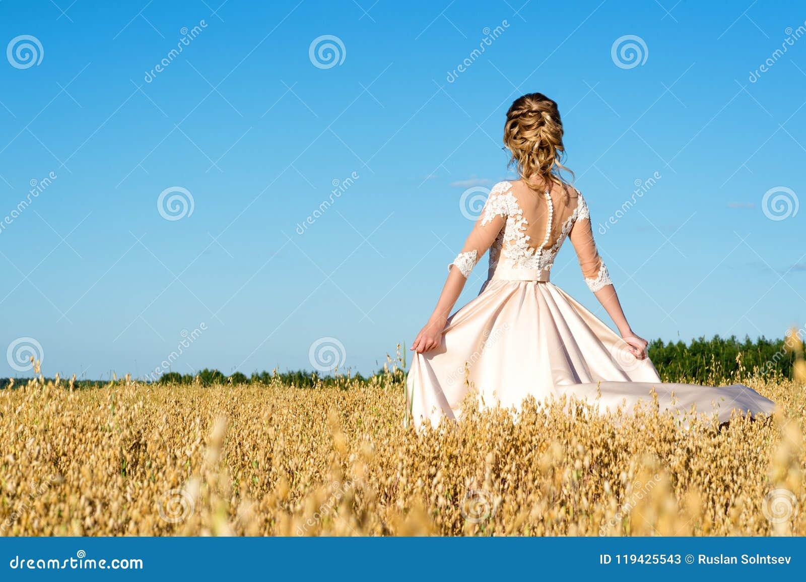 Menina bonita no vestido bege no centeio do campo, vista traseira