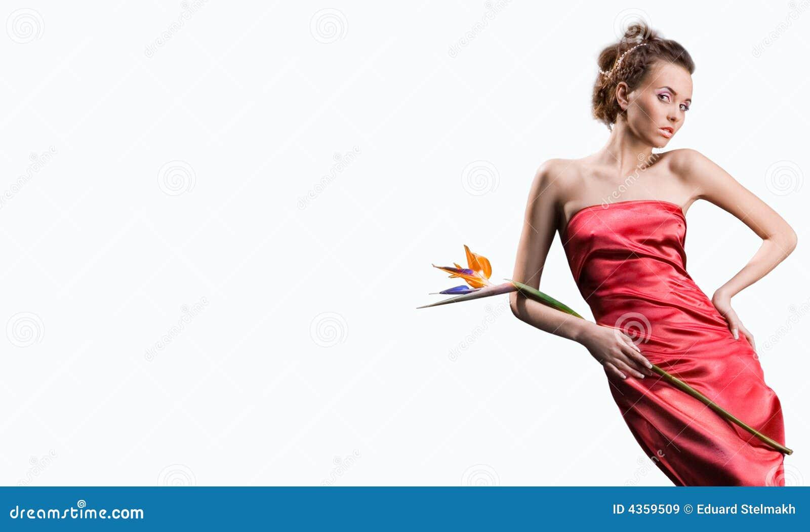 A menina bonita no vestido vermelho prende a flor exótica