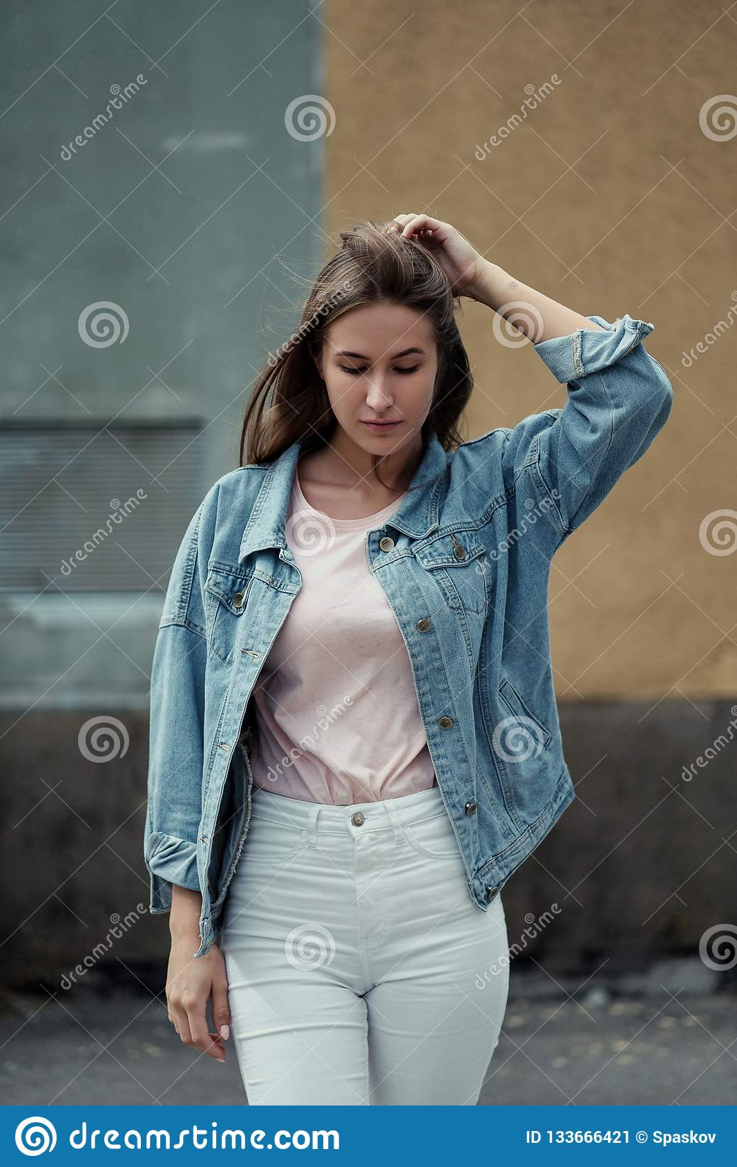Menina bonita nova com cabelo longo em um revestimento do t-shirt e da sarja de Nimes no fundo do muro de cimento do vintage