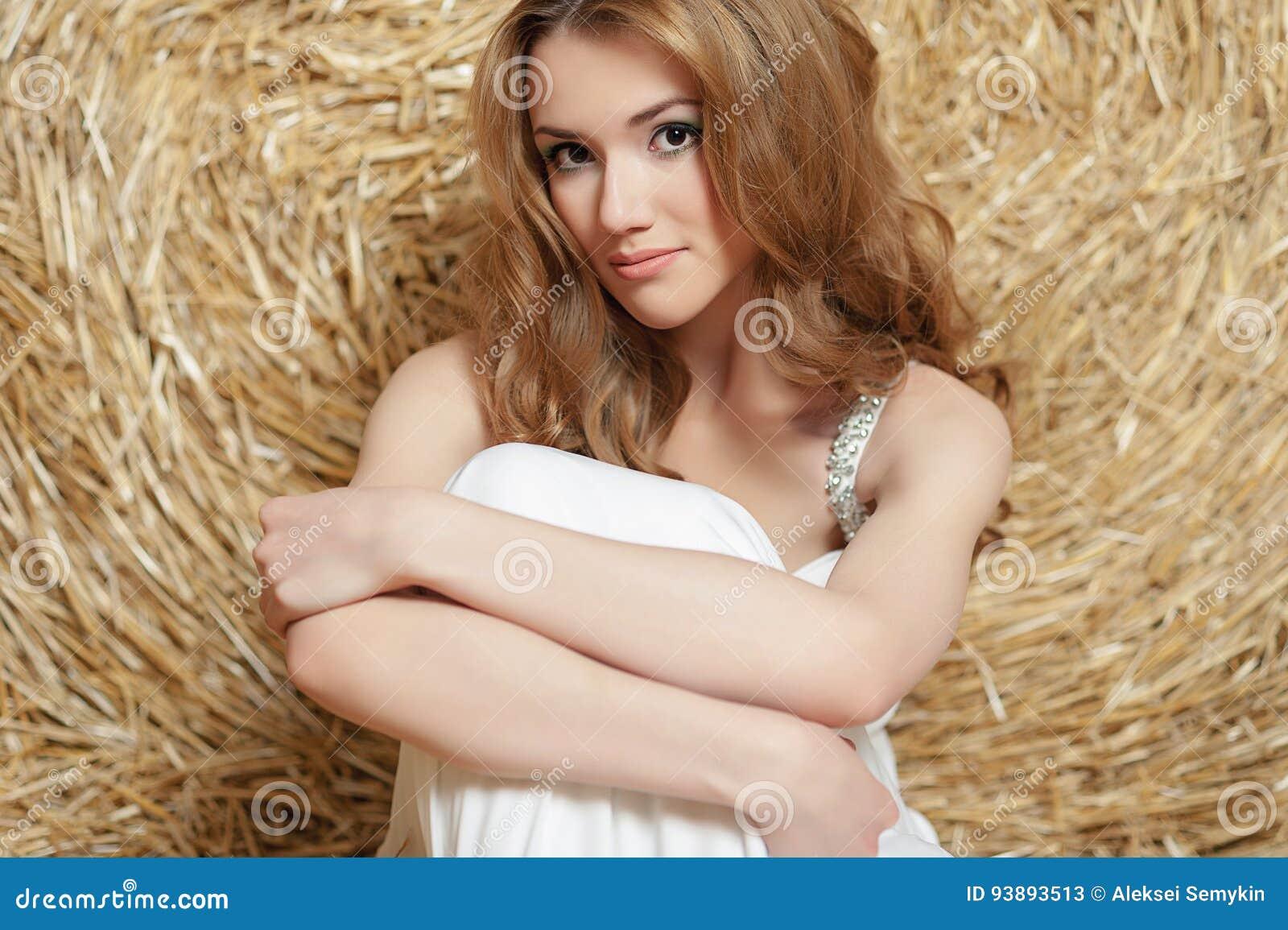 84587a10ac5b A menina nova, bonita com cabelo vermelho em um vestido branco está sentando -se perto de um monte de feno verão na vila