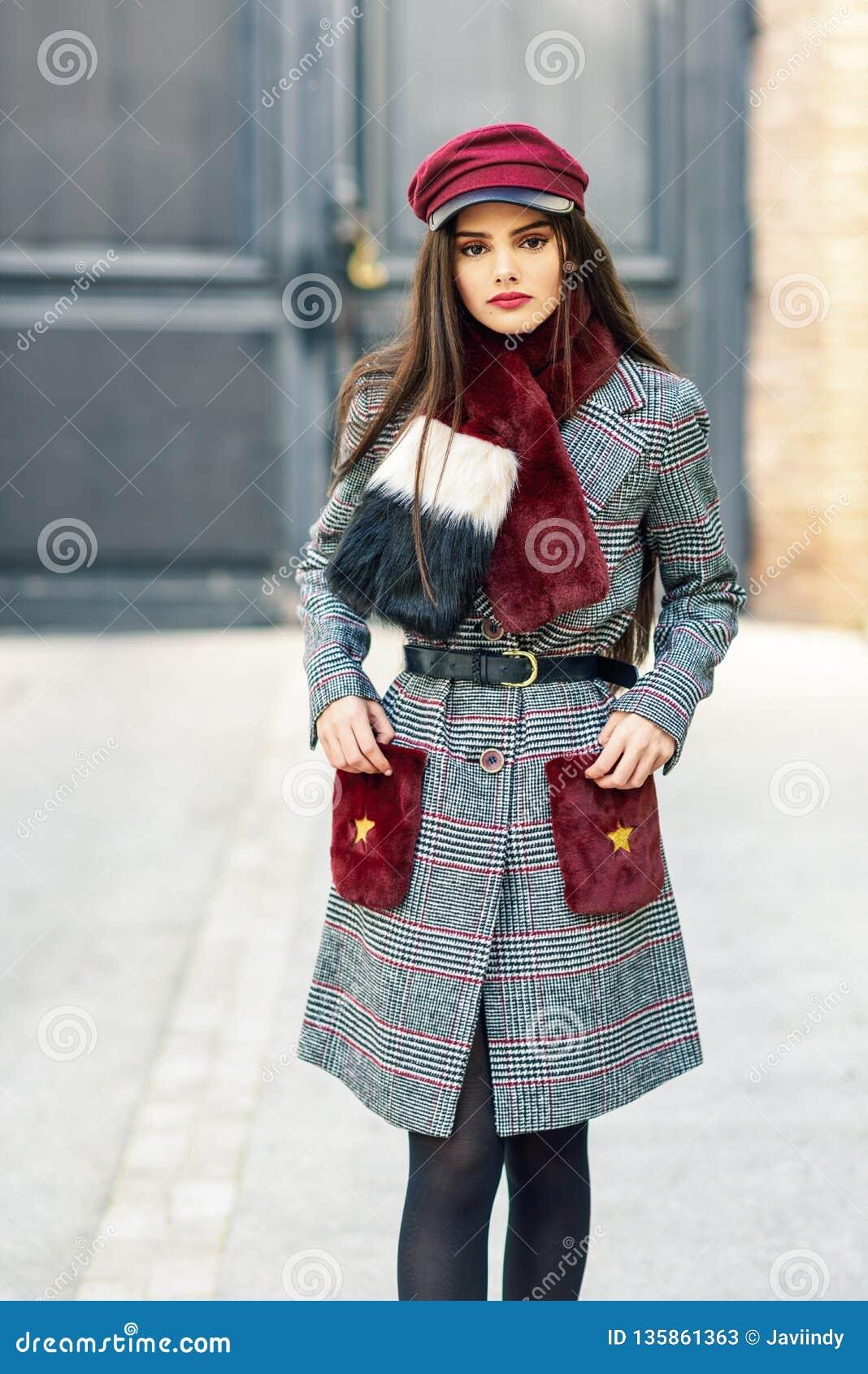 Menina bonita nova com o cabelo muito longo que olha o revestimento vestindo do inverno da câmera