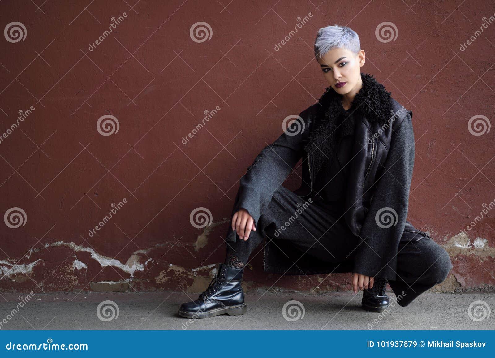 Menina bonita nova da forma que dispara fora perto da parede de tijolo em casa