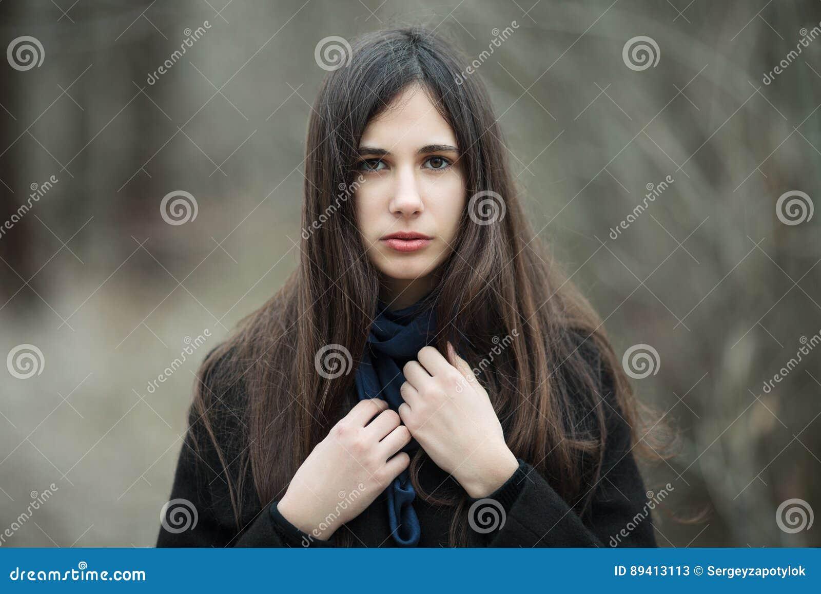 Menina bonita nova em um fim azul do lenço do revestimento preto acima no outono/mola Forest Park Uma menina moreno elegante com