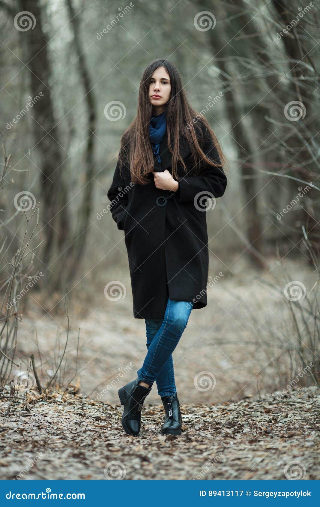 Menina bonita nova em um outono do lenço azul preto do revestimento/mola de exploração Forest Park Uma menina moreno elegante com
