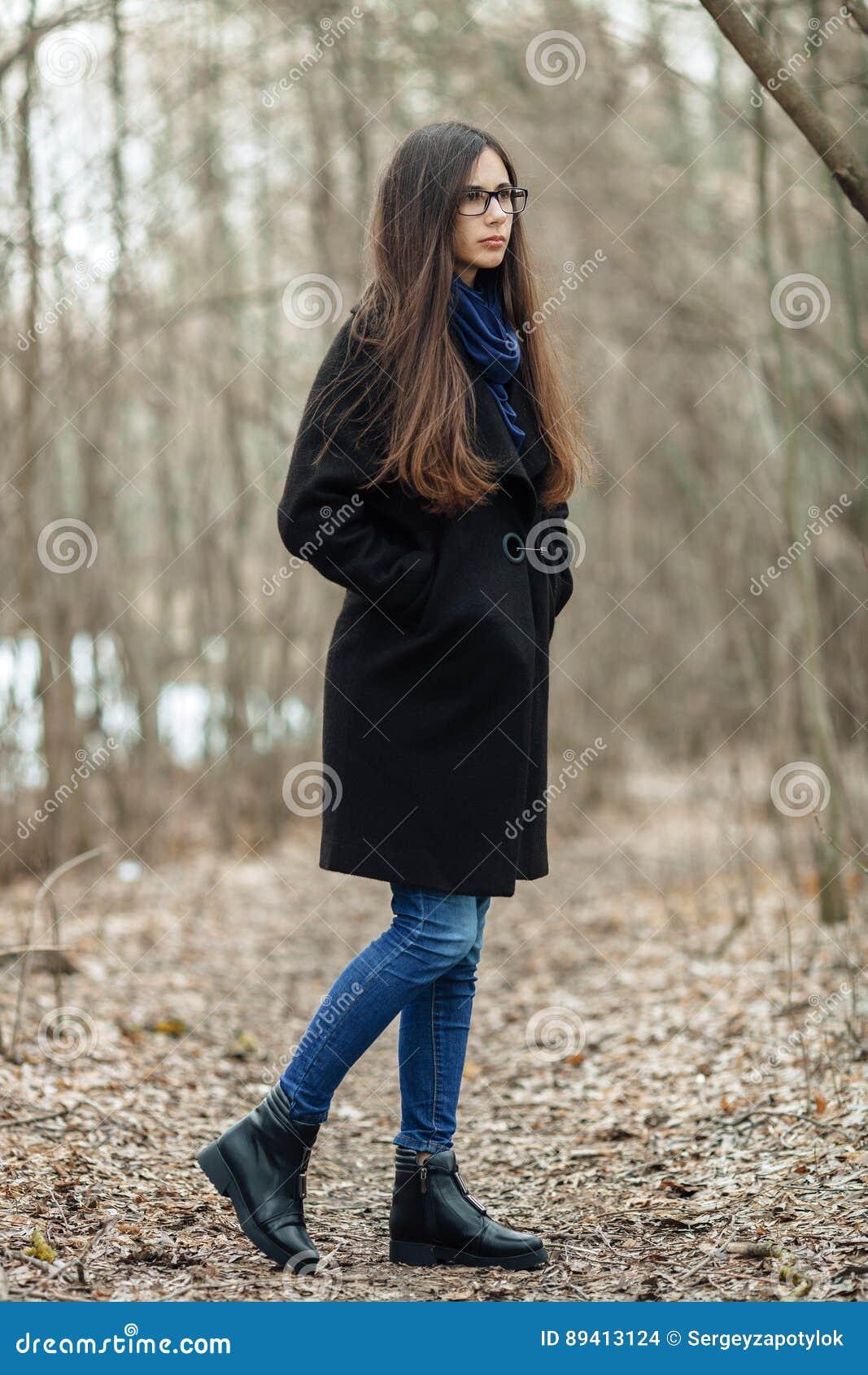 Menina bonita nova em vidros azuis de um lenço do revestimento preto que anda no outono/mola Forest Park Uma menina moreno elegan