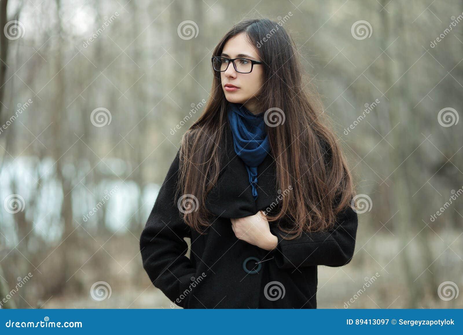Menina bonita nova em vidros azuis de um lenço do revestimento preto que explora o outono/mola Forest Park Uma menina moreno eleg