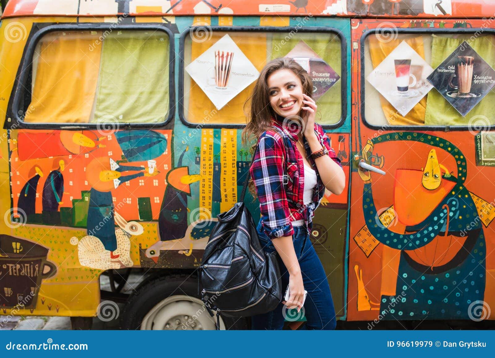 Menina bonita nova na roupa à moda na frente do ônibus quebrado velho que levanta na rua da cidade