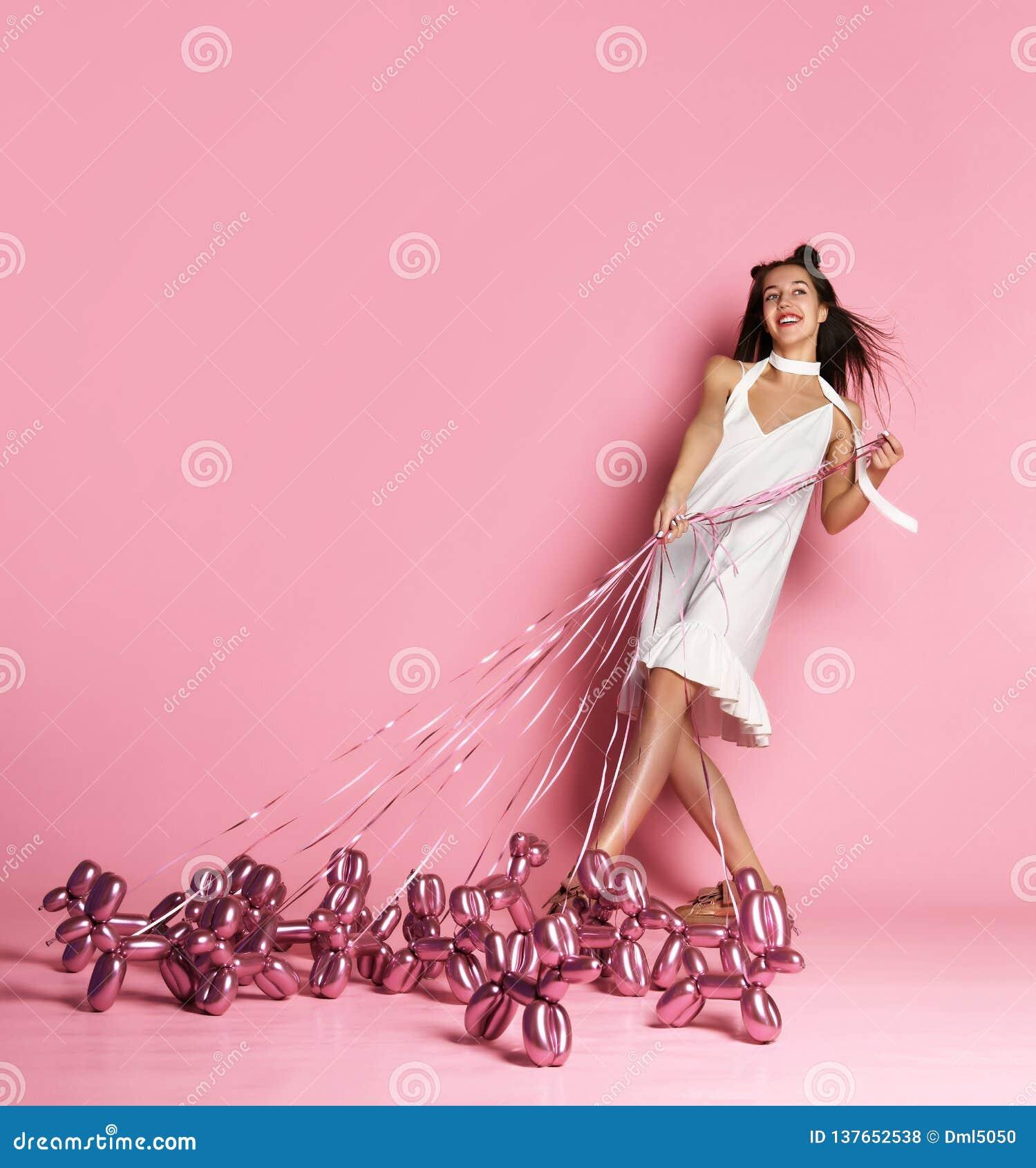 A menina bonita nova no vestido branco anda os cães infláveis do balão em um sorriso feliz da trela