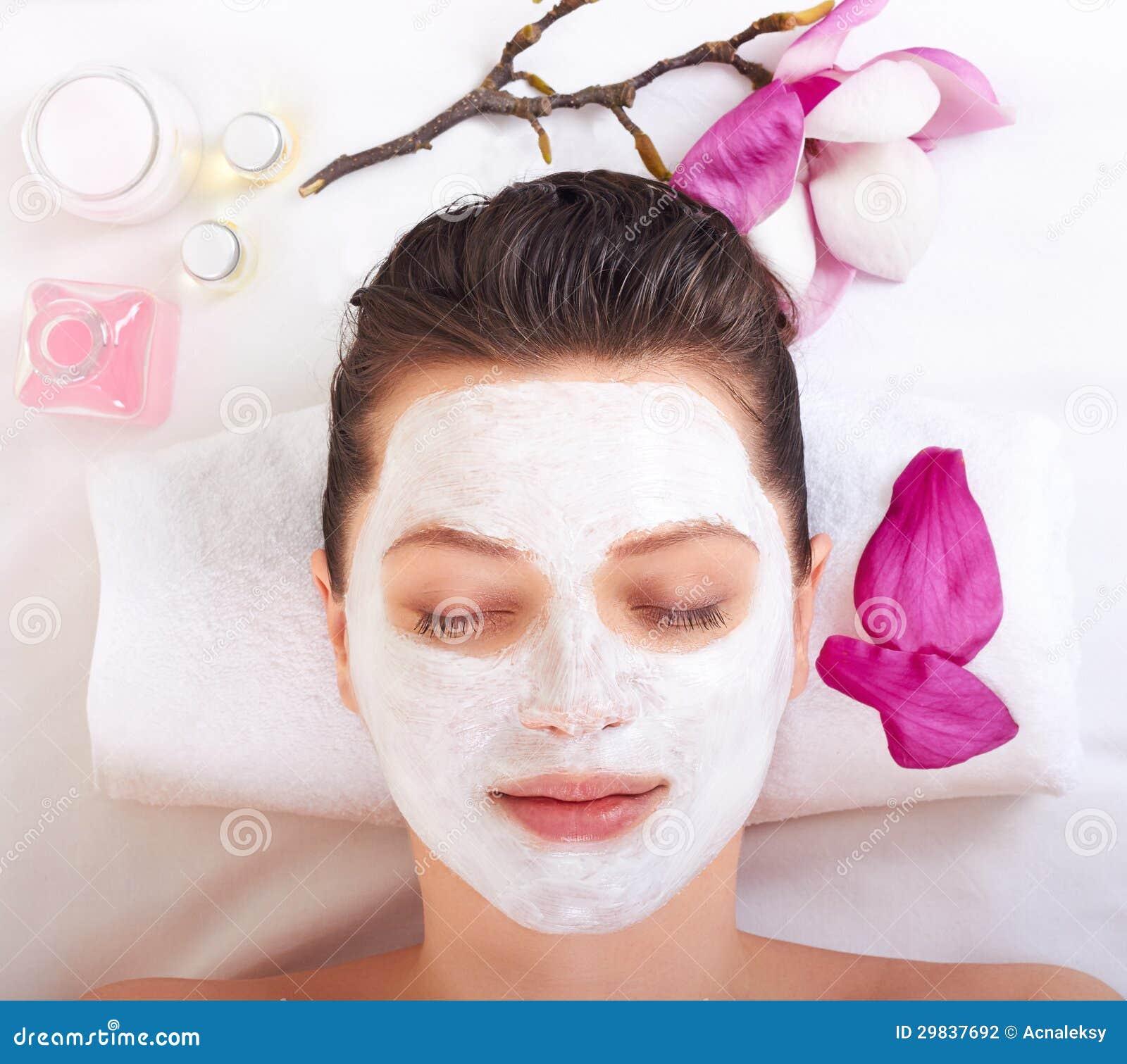 Menina bonita nova que recebe a máscara facial cor-de-rosa