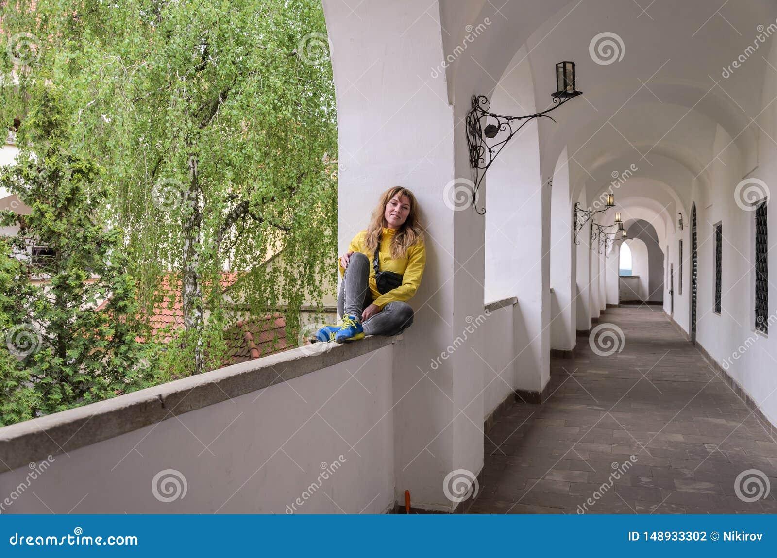 Menina bonita nova que senta-se em uma janela arqueada em um castelo antigo