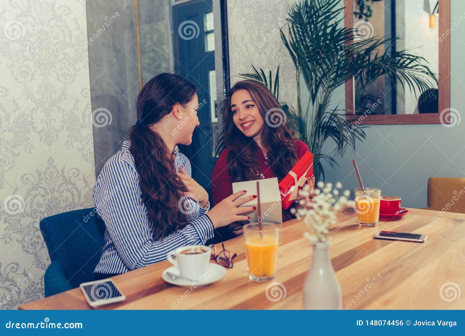 Menina bonita nova que senta-se no café com seu amigo e que recebe um presente