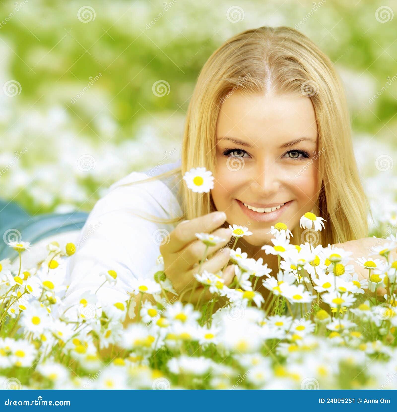 Menina bonita que aprecia o campo da margarida