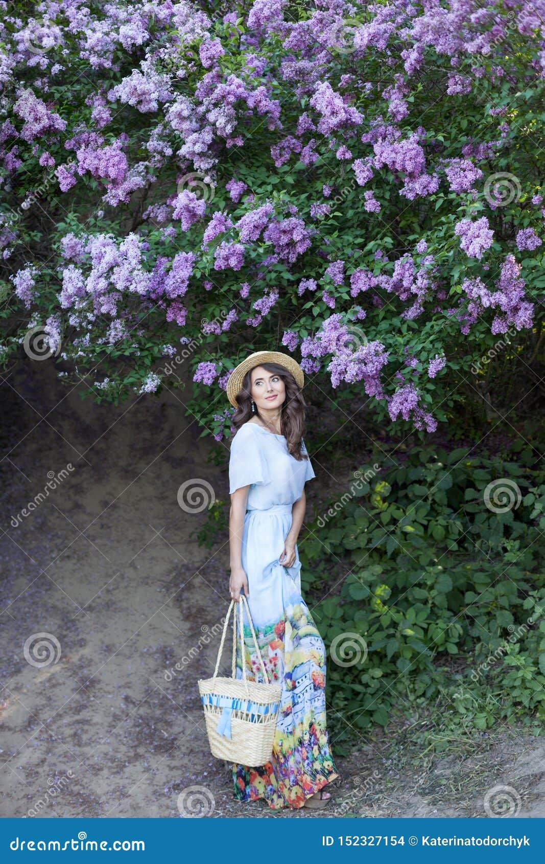 Menina bonita que aprecia o cheiro do lilás em um dia de verão Conceito da aromaterapia e da mola Uma menina bonita, uma mulher b