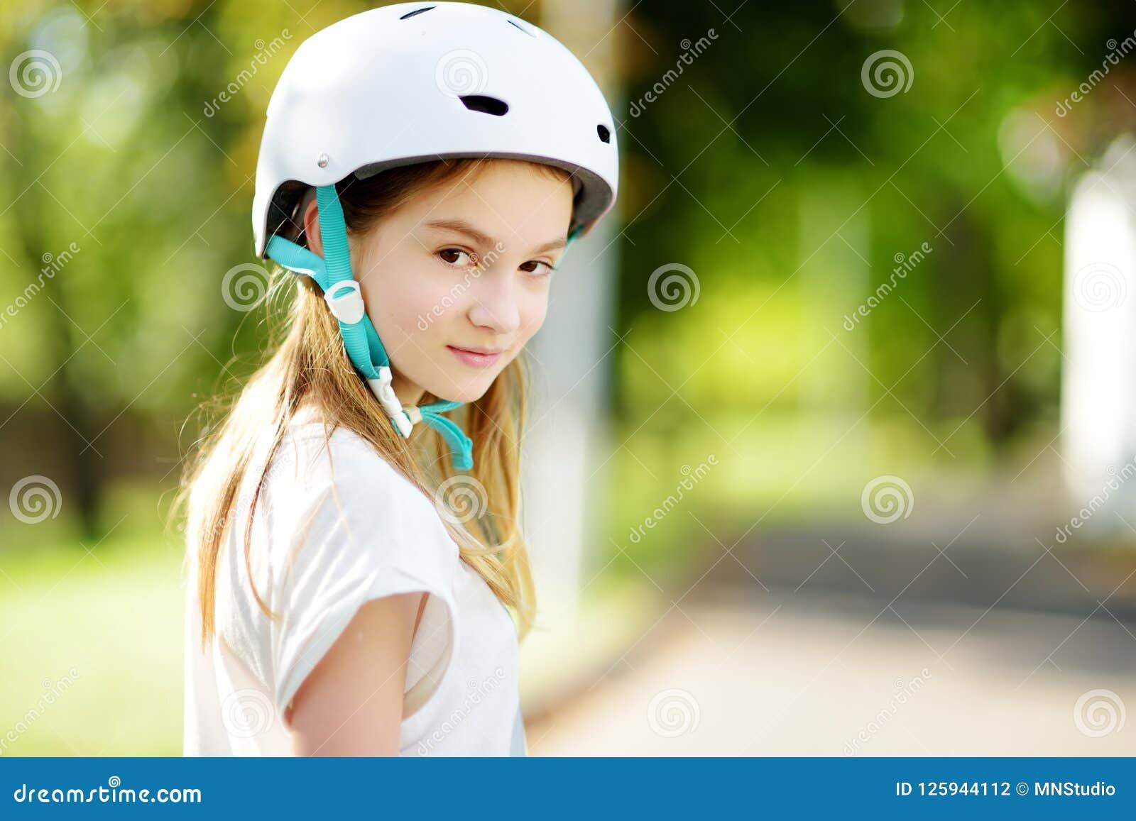 Menina bonita que aprende ao patim de rolo no dia de verão em um parque Capacete de segurança vestindo da criança que aprecia o o
