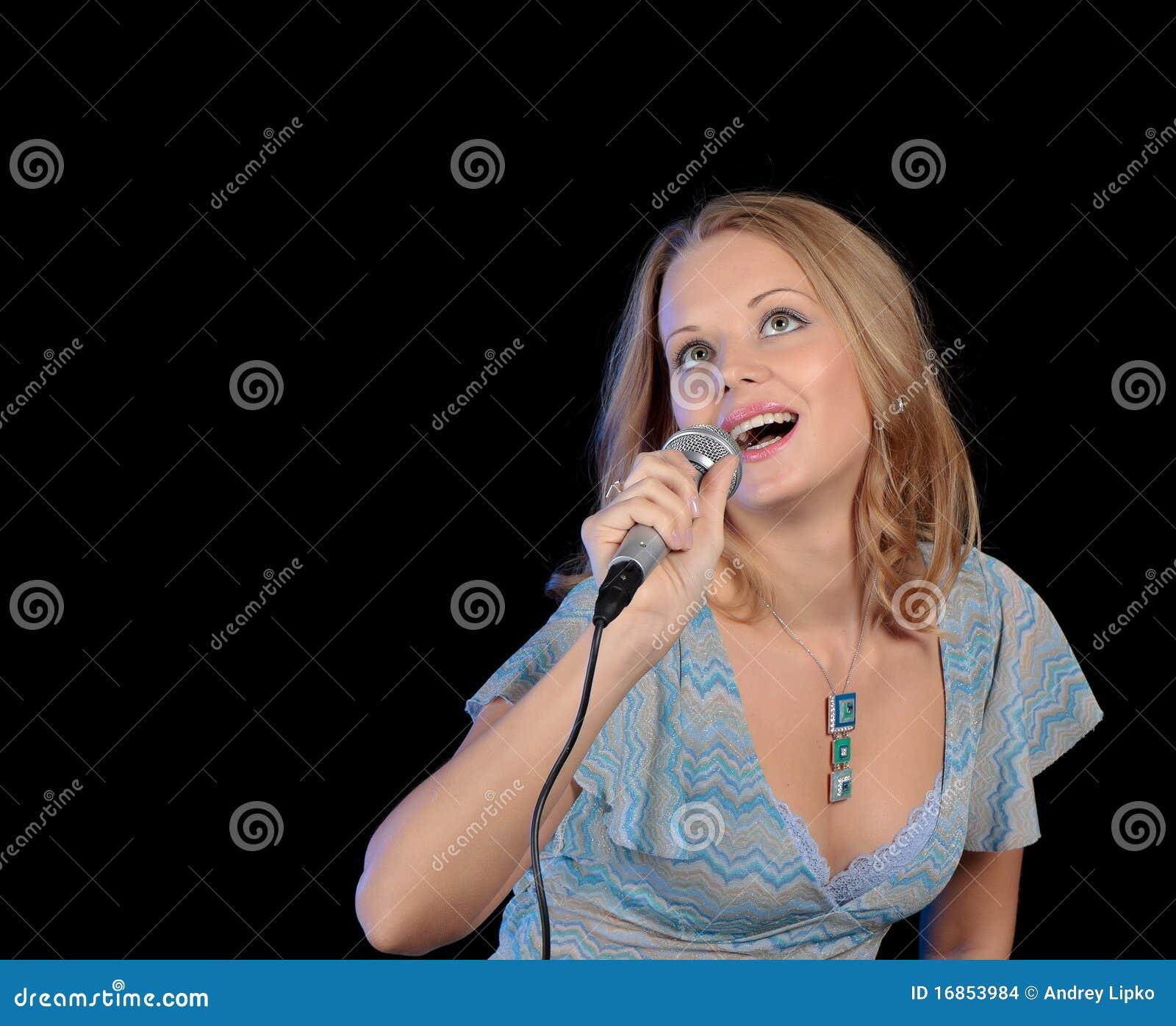 Menina bonita que canta em um microfone