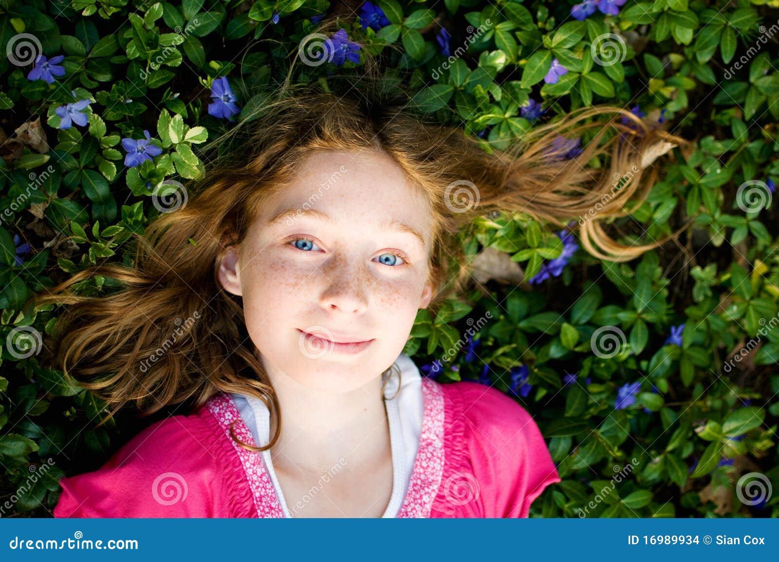 Menina bonita que coloca na planta da pervinca