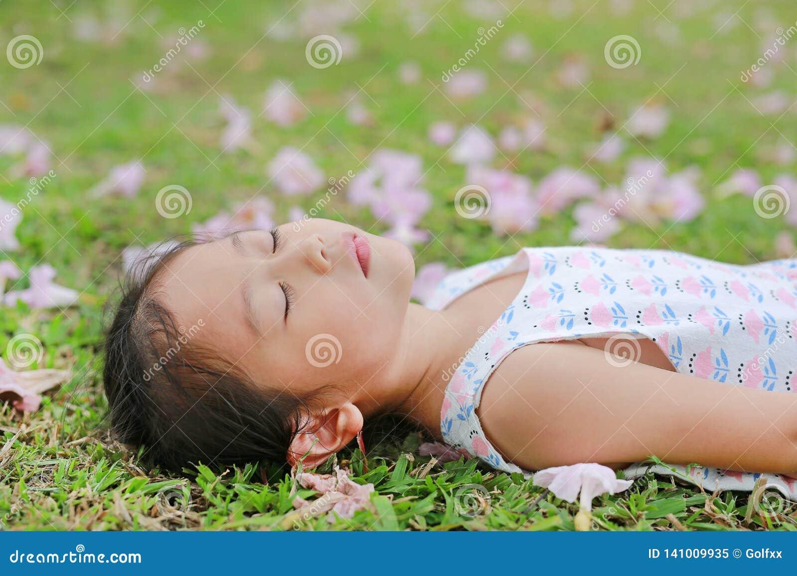 Menina bonita que dorme na grama verde com a flor do rosa da queda no jardim exterior