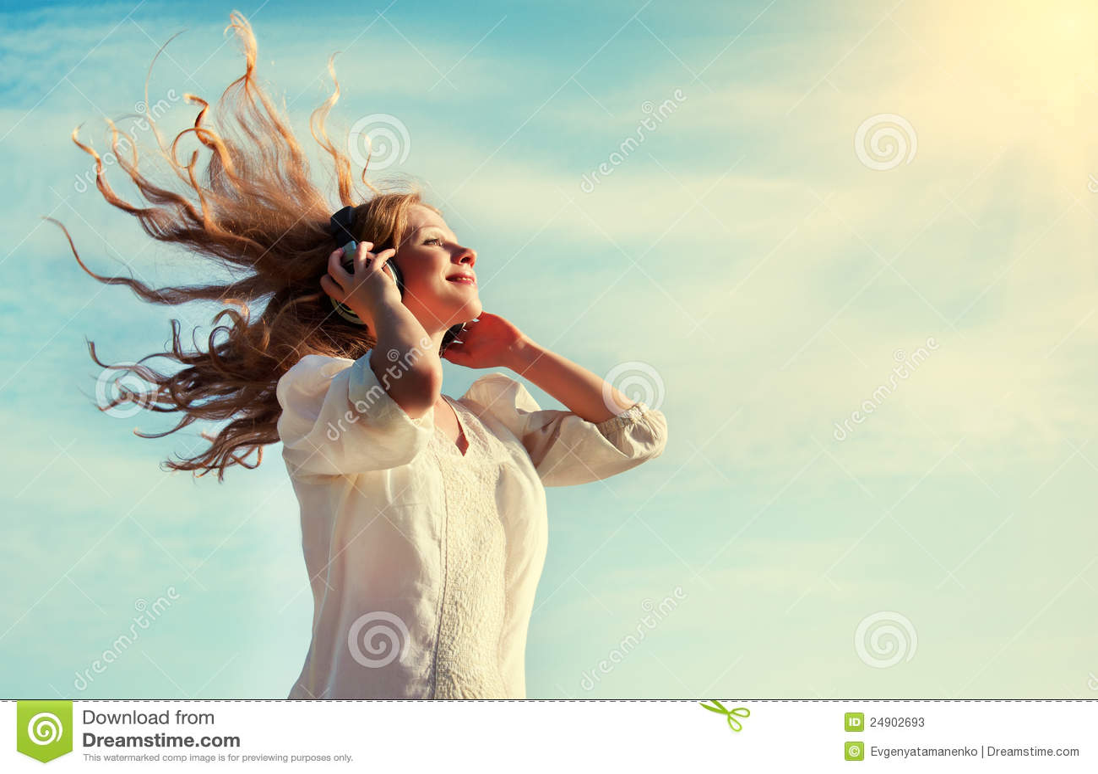 Menina bonita que escuta a música em auscultadores