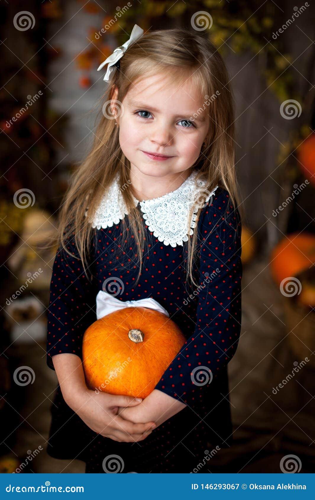 Menina bonita que guarda uma abóbora