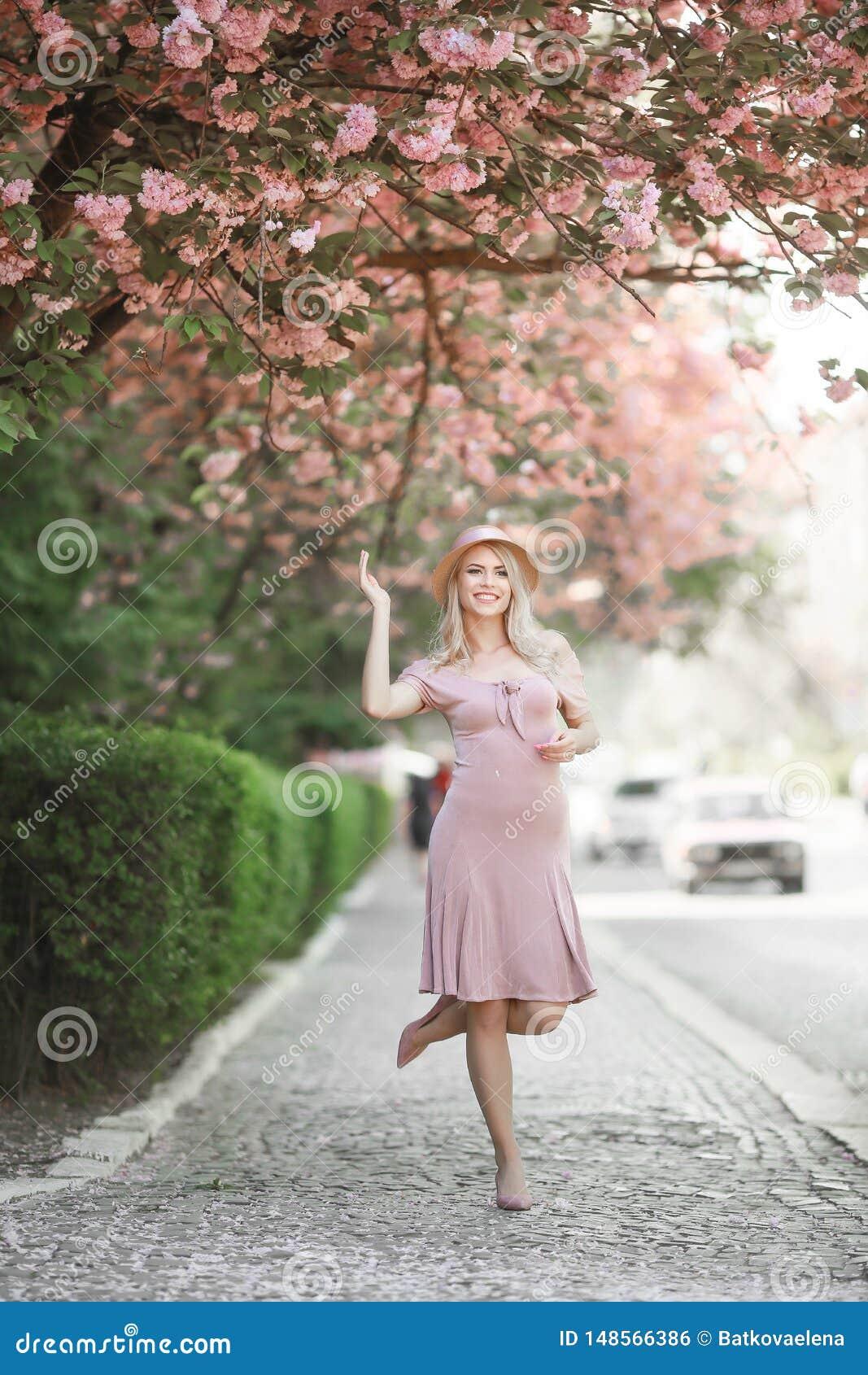 Menina bonita que levanta no p?ssego e em Sakura Flowers Blooming Garden cor-de-rosa Sorriso atrativo novo da mulher, levantando