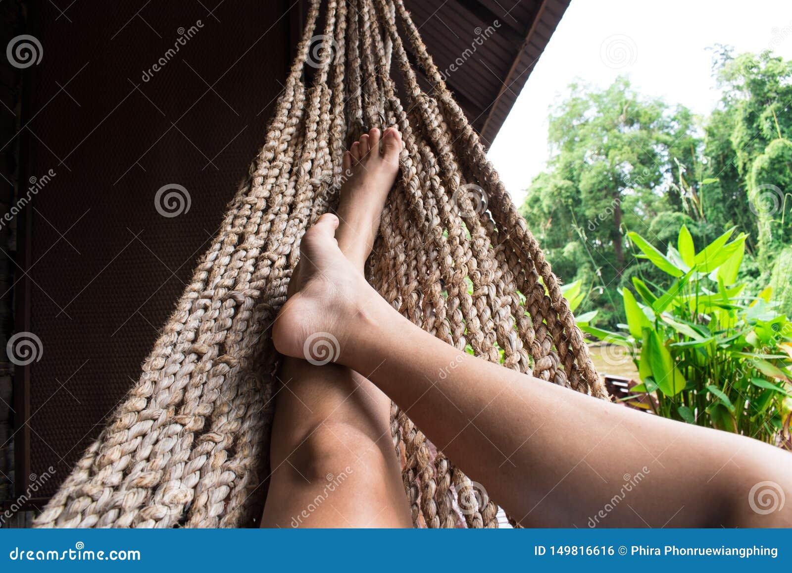 Menina bonita que relaxa em uma rede em casa