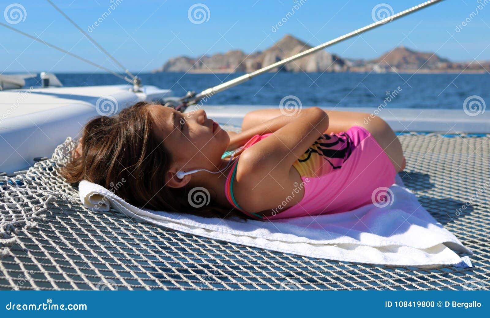 Menina bonita que relaxa no veleiro ao escutar a música no oceano