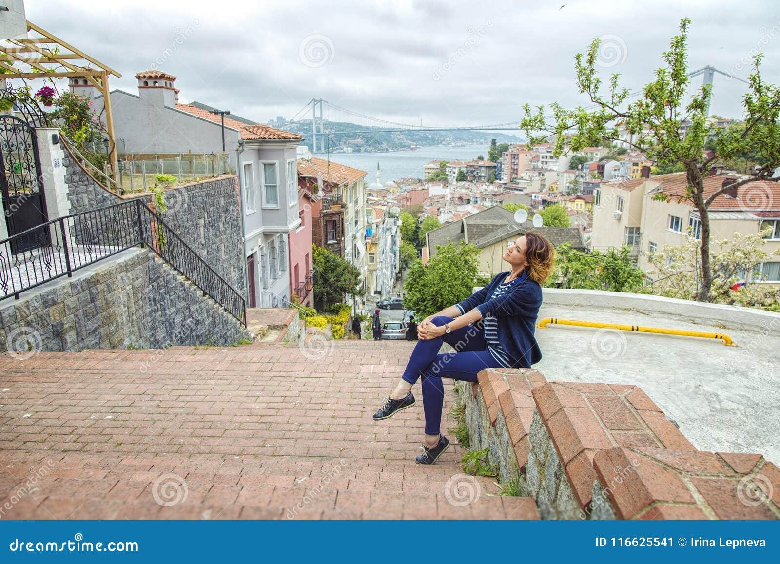 Menina bonita que senta-se em uma escada no distrito de Kuzguncuk