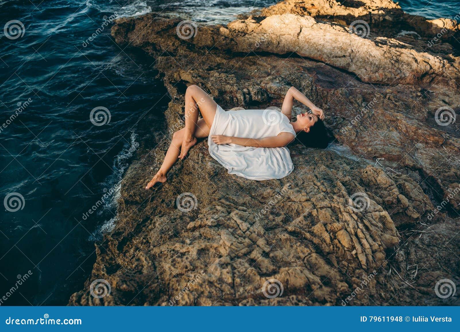 Menina bonita que senta-se em uma rocha no mar da praia