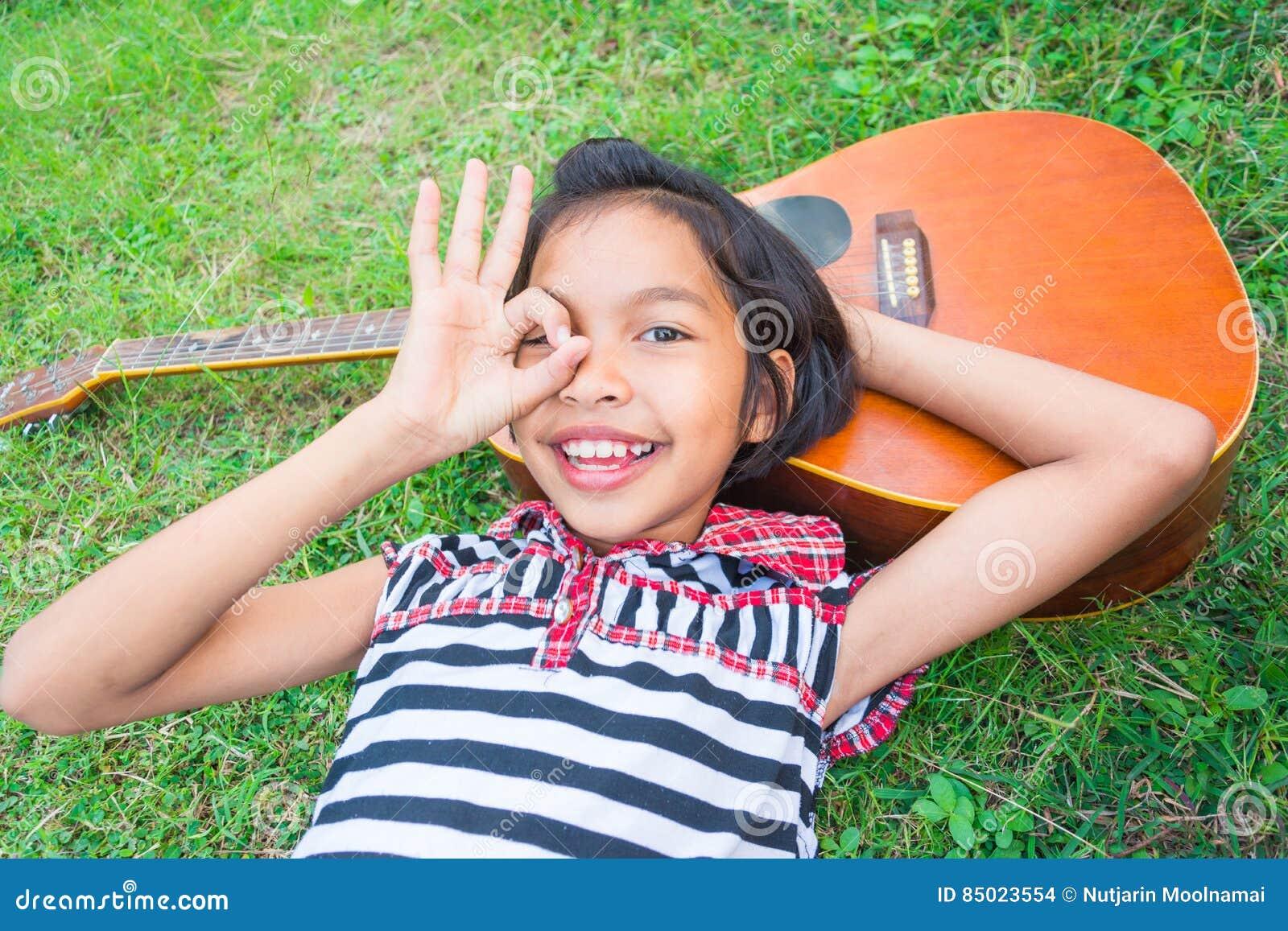 Menina bonita que sorri com a guitarra, encontrando-se para baixo na grama