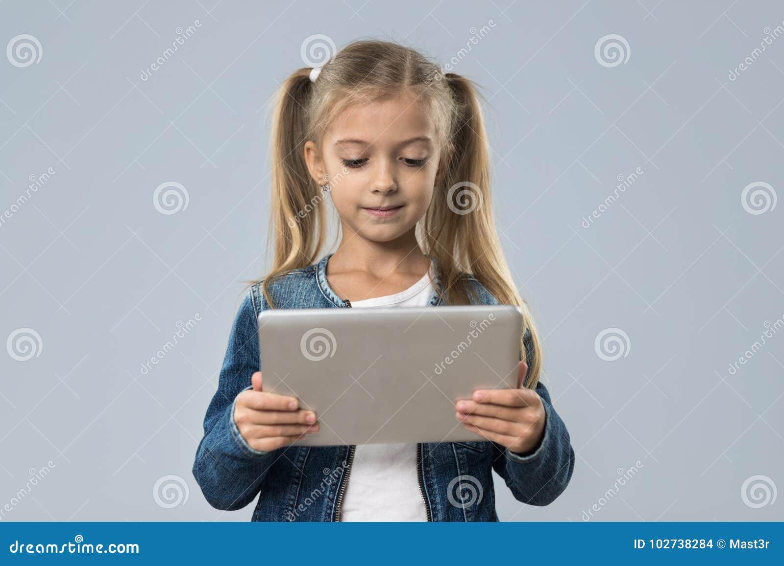 Menina bonita que usa o revestimento de sorriso feliz das calças de brim do desgaste do tablet pc isolado