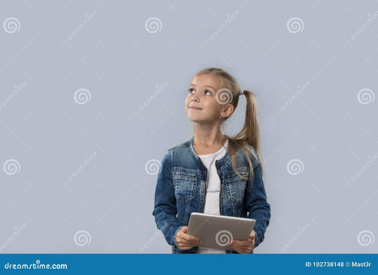 Menina bonita que usa o tablet pc que olha acima para copiar o sorriso feliz do espaço isolado