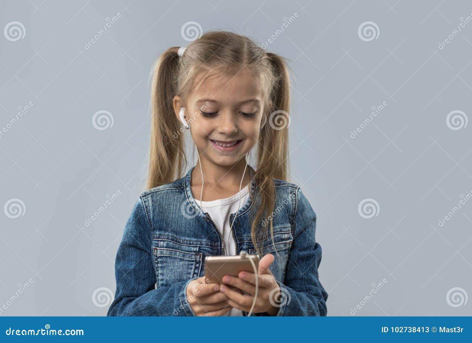 A menina bonita que usa o telefone esperto da pilha escuta sorriso feliz dos fones de ouvido do desgaste da música isolado