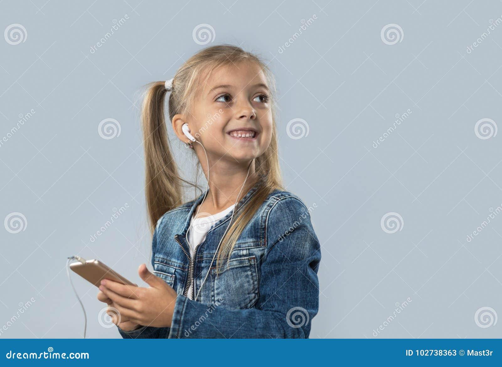 A menina bonita que usa o telefone esperto escuta olhar de sorriso feliz dos fones de ouvido do desgaste da música para copiar o