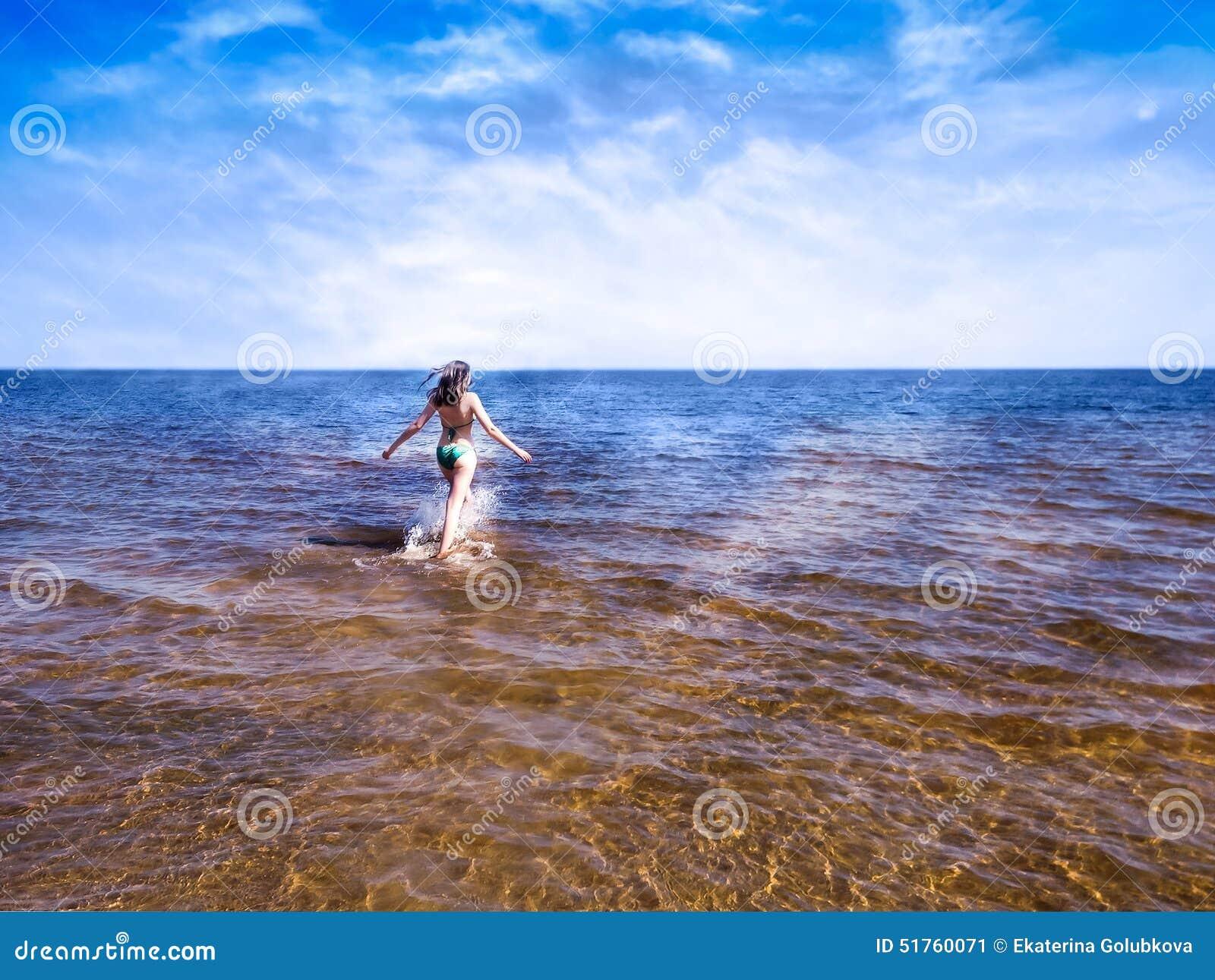 Menina bonita que vai sobre brilhar a água transparente do mar azul
