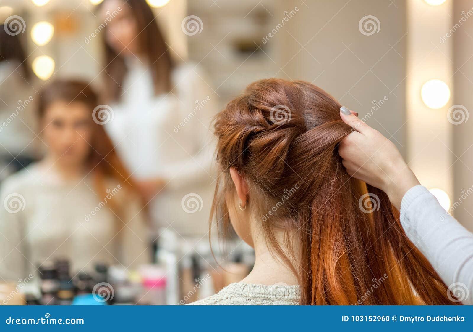 A menina bonita, ruivo com cabelo longo, cabeleireiro tece uma trança francesa, em um salão de beleza