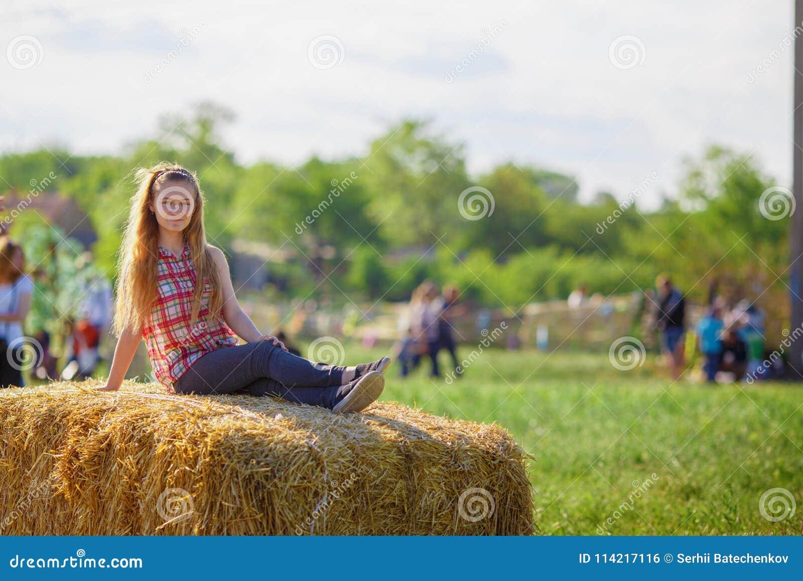A menina bonita senta-se em um monte de feno