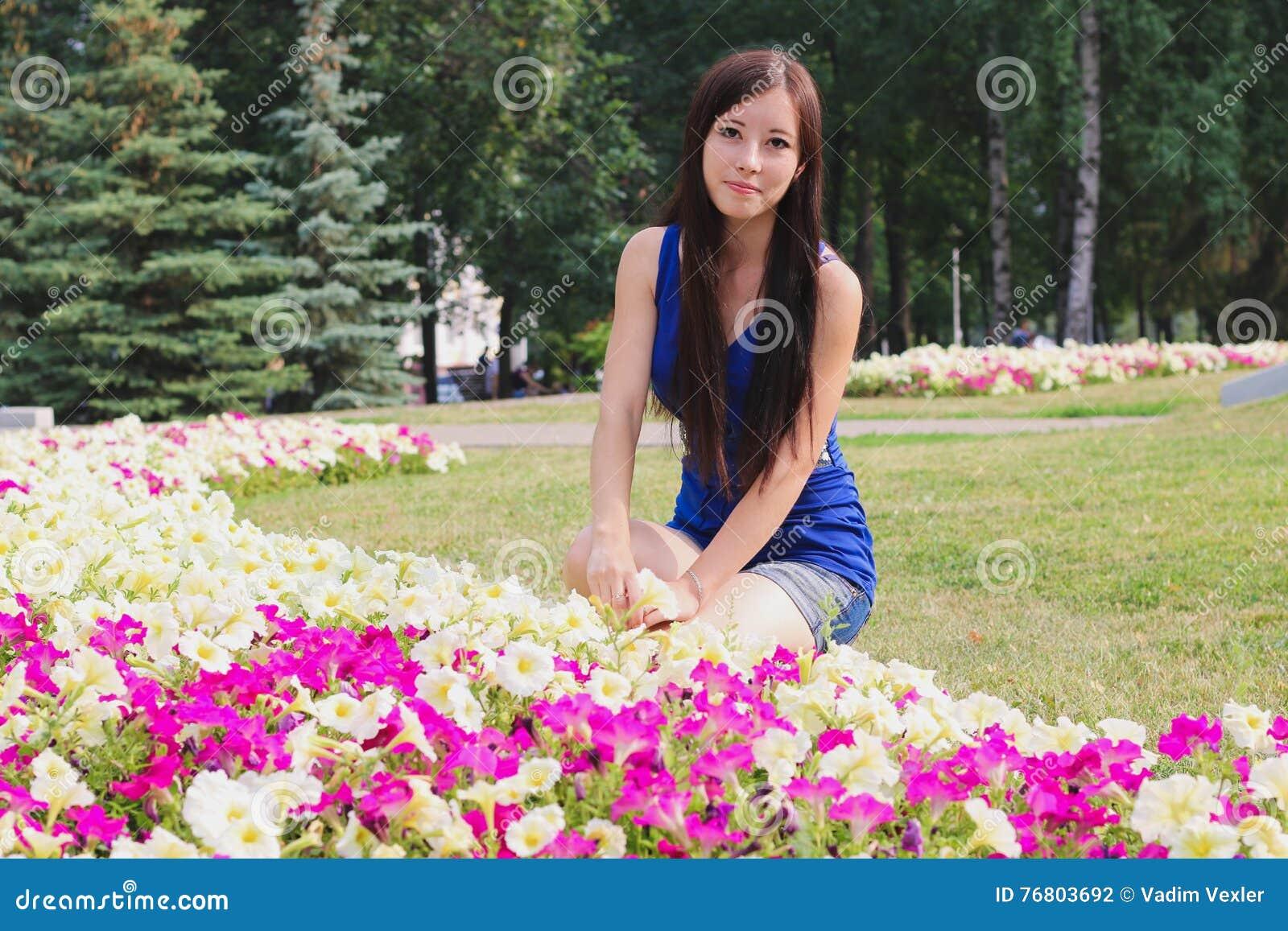 A menina bonita senta-se perto dos canteiros de flores