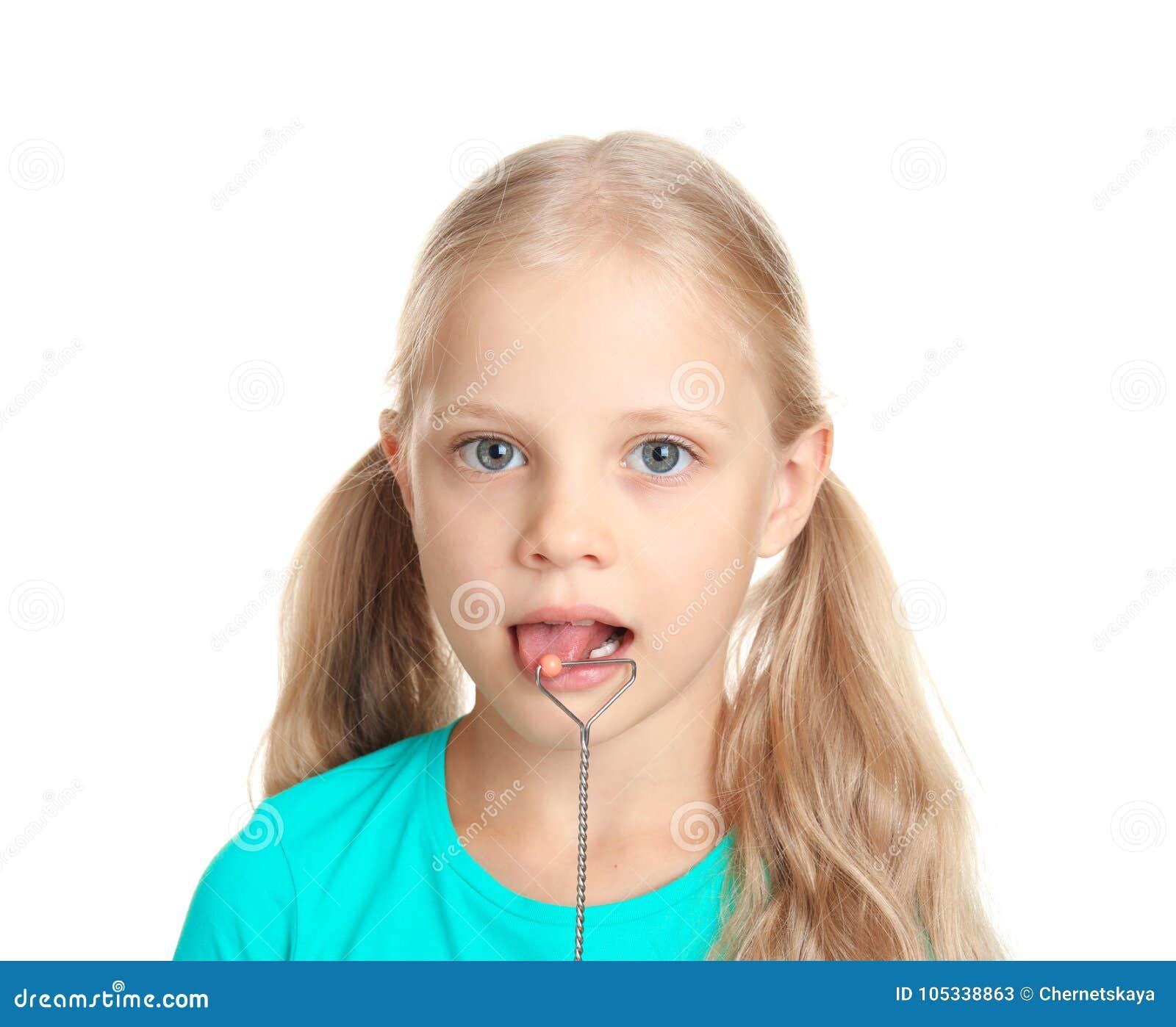 Menina bonito com ponta de prova logopedic para a correção de discurso no fundo branco