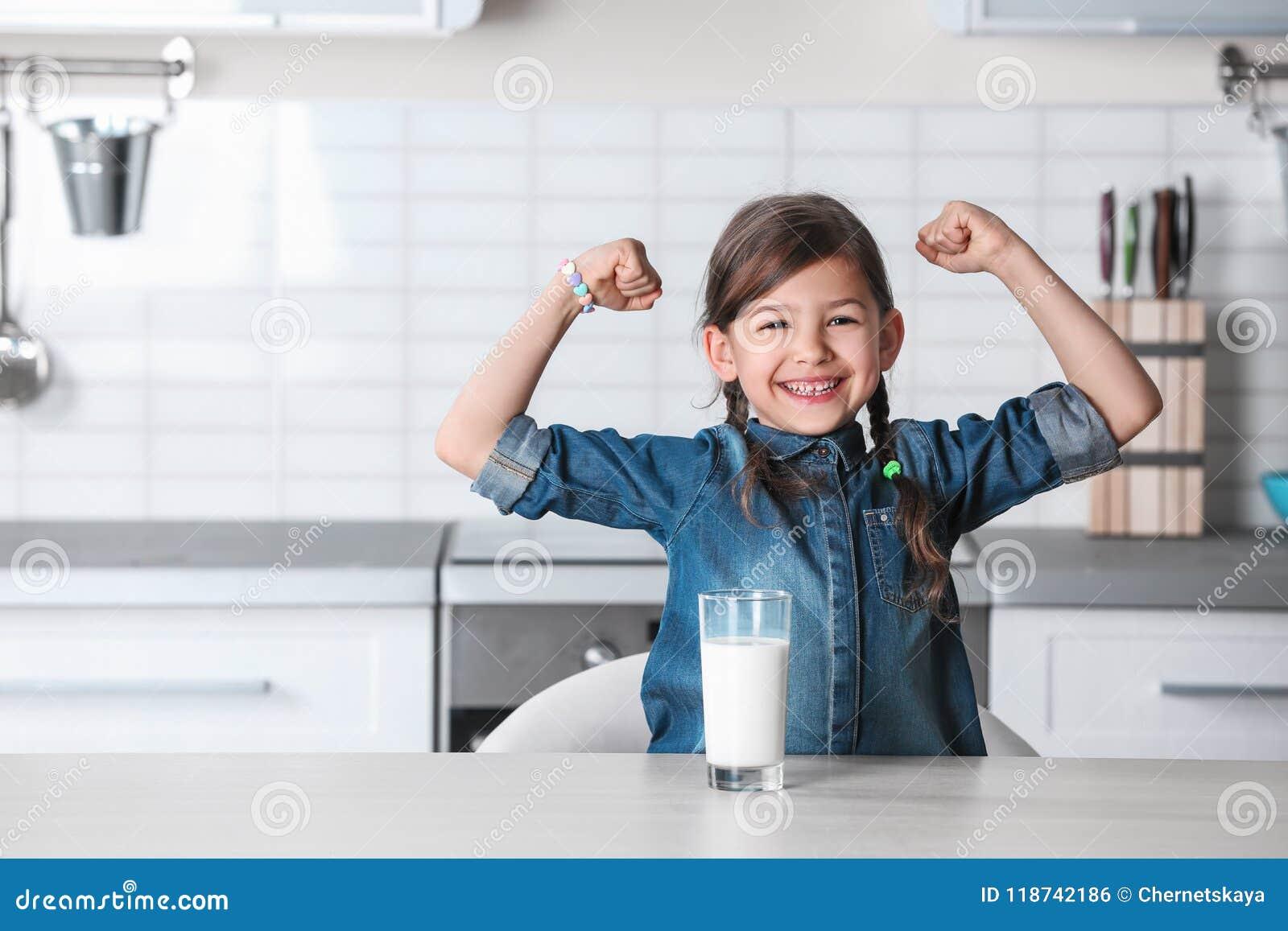 Menina bonito com vidro do leite na tabela na cozinha