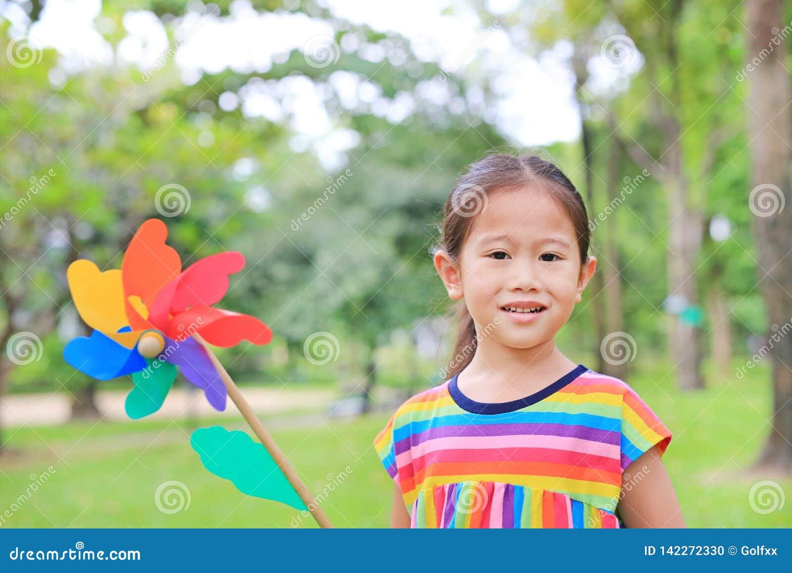 Menina bonito da criança pequena com a turbina eólica no jardim