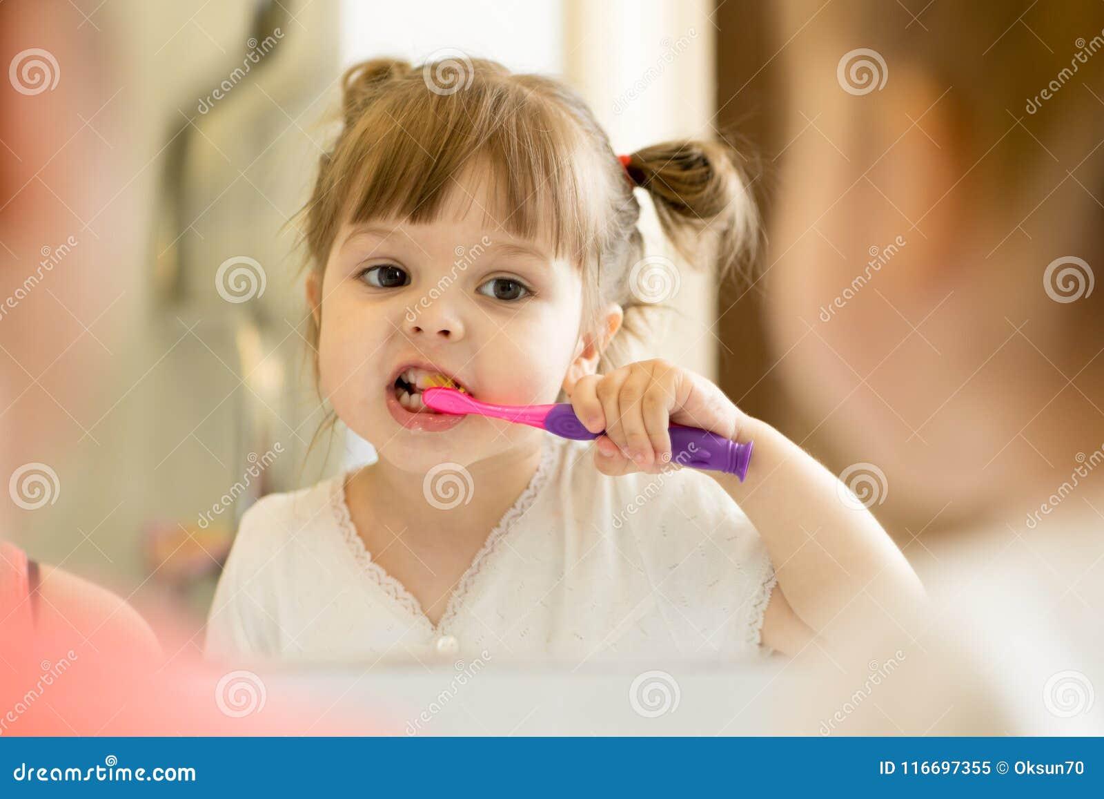 Menina bonito da criança que olha o espelho usando os dentes da limpeza da escova de dentes no banheiro cada manhã e noite