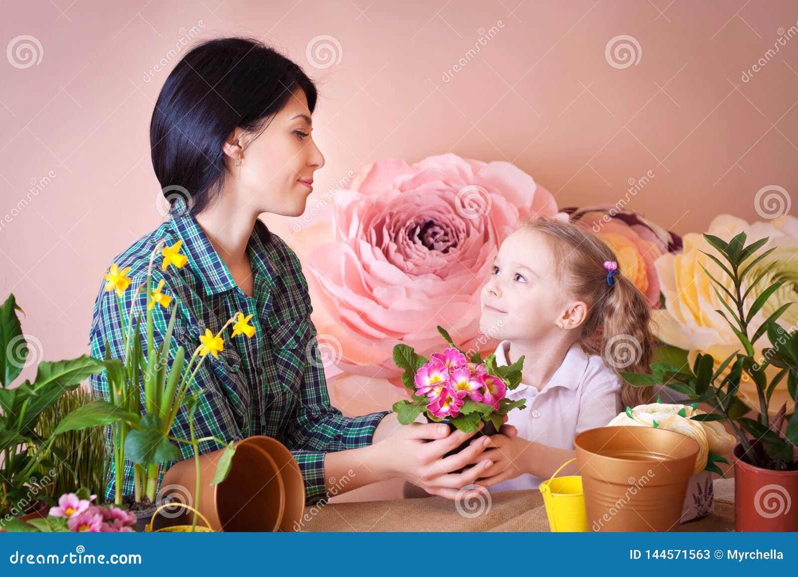 A menina bonito da crian?a ajuda sua m?e a importar-se com plantas